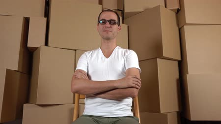 self storage : Geeky owner of small internet shop sitting against multiple carton stacks. 4K clip