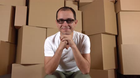 self storage : Confident smiling owner of internet shop sitting against multiple carton stacks. 4K clip