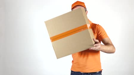 перевозка груза : Delivery man in orange uniform throwing a big parcel at the camera. Light gray backround, slow motion studio shot Стоковые видеозаписи