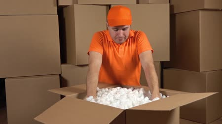 paketleme : Warehouse worker in orange uniform unboxing big carton full of soft packaging material. Shockproof container. Multiple boxes background. Slow motion video
