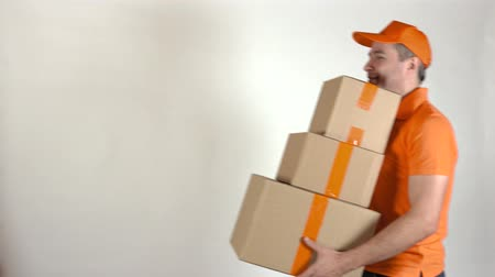 posta kutusu : Delivery man in orange uniform delivering big stack of cardboard boxes. Light gray backround, 4K studio shot