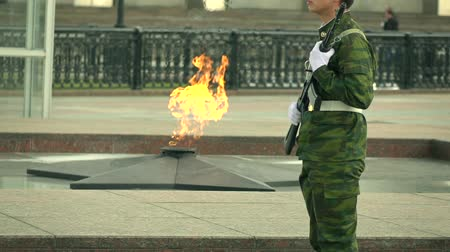 muhterem : Memorial fire and armed guard in camouflage uniform. Super slow motion long shot Stok Video