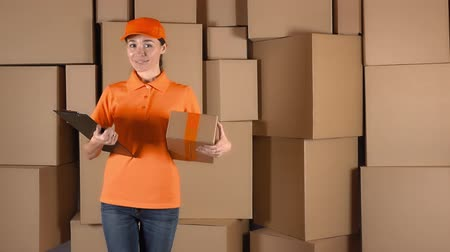 balík : Female courier in orange uniform delivering a parcel to wrong address. Mistake or inaccuracy concept, 4K shot