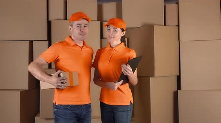 lojistik : Couriers in orange uniform standing against brown cartboard boxes backround. Delivery company personel, 4K clip Stok Video