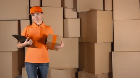 dağıtım : Pretty female courier in orange uniform delivering a parcel against cardboard boxes stacks backround. 4K studio video