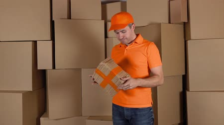 posta kutusu : Delivery man in orange uniform delivering damaged parcel to customer. Brown cartons background. Flaw and unprofessional work concepts. 4K studio shot