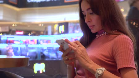 наркомания : Pretty brunette girl in pink using her telephone in a cafe. Mobile phone addiction. 4K video