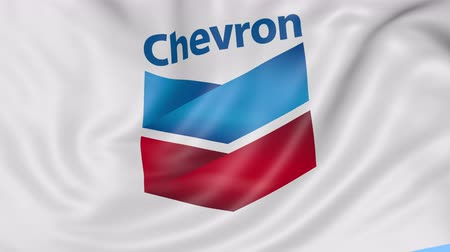 refining : Close up of waving flag with Chevron Corporation logo, seamless loop, blue background. Editorial animation.