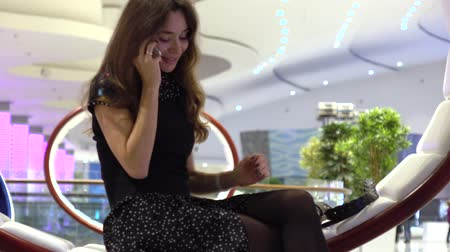 hívó : Beautiful young woman in black talking on her phone in a modern interior. 4K video