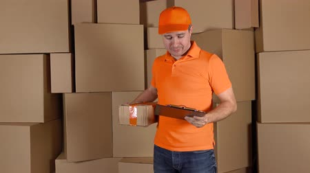 paket : Man in orange uniform delivering heavily damaged parcel to customer. Brown cartons background. Unprofessional work and regret concept. 4K shot