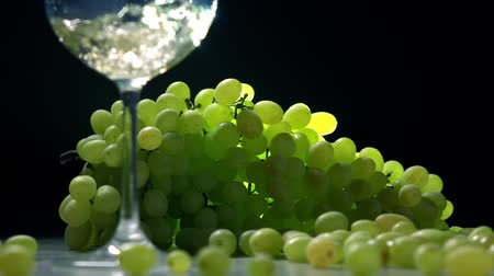şarap cam : Pouring white wine into glass against the bunch of green grapes. Winemaking concept. Super slow motion shot