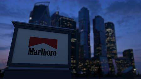 richmond : Street signage board with Marlboro logo in the evening. Blurred business district skyscrapers background. Stock Footage