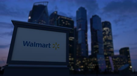 walmart : Street signage board with Walmart logo in the evening. Blurred business district skyscrapers background.