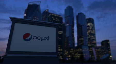 pepsico : Street signage board with Pepsi logo in the evening. Blurred business district skyscrapers background.
