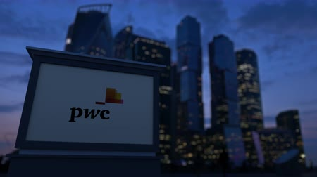 pwc : Street signage board with PricewaterhouseCoopers PwC logo in the evening. Blurred business district skyscrapers background. Stock Footage