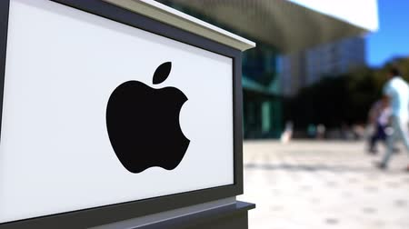 apple headquarter : Street signage board with Apple Inc. logo. Blurred office center and walking people background. Editorial  3D rendering