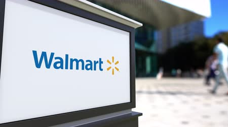 walmart : Street signage board with Walmart logo. Blurred office center and walking people background. Stock Footage