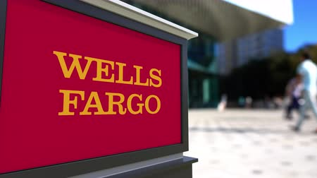 ипотека : Street signage board with Wells Fargo logo. Blurred office center and walking people background. Editorial  3D rendering