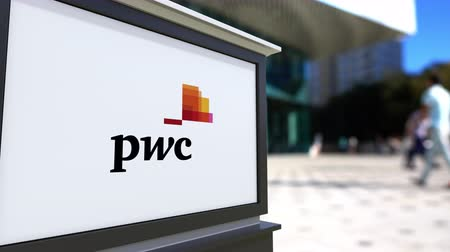 pwc : Street signage board with PricewaterhouseCoopers PwC logo. Blurred office center and walking people background. Editorial  3D rendering