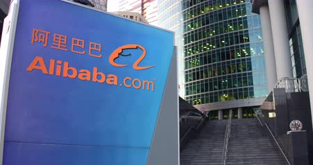 common : Street signage board with Alibaba.com logo. Modern office center skyscraper and stairs background.