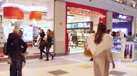 előléptetés : WARSAW, POLAND - DECEMBER, 18, 2016.steadicam shot of a girl with angel wings walking in a modern shopping mall. Christmas sale time