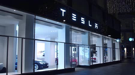 tesla car : VIENNA, AUSTRIA - DECEMBER, 24 Steadicam shot of hi-tech Tesla electric cars showroom at night. Stock Footage
