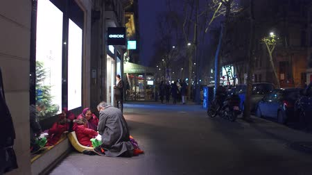 andarilho : PARIS, FRANCE - DECEMBER, 31, 2016. Local man giving present to immigrant little girl sitting on the street. Immigration tolerance and kindness. Vídeos