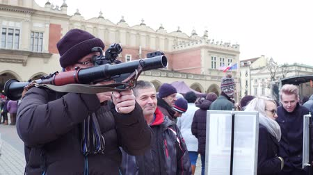 sivil : KRAKOW, POLAND - JANUARY, 14, 2017 Man examines RPG grenade launcher at military show. Stok Video