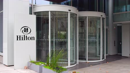 hilton : Street signage board with Hilton Hotels & Resorts logo. Modern office building. Editorial 3D rendering