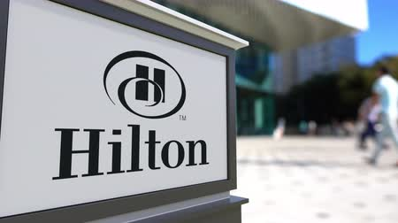 hilton : Street signage board with Hilton Hotels Resorts logo. Blurred office center and walking people background. Editorial 3D rendering