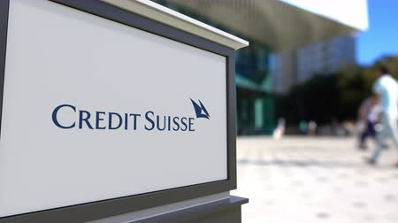 credit suisse : Street signage board with Credit Suisse Group logo. Blurred office center and walking people background. Editorial 3D rendering