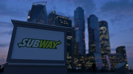 franczyza : Street signage board with Subway logo in the evening.  Blurred business district skyscrapers background. Editorial 3D rendering