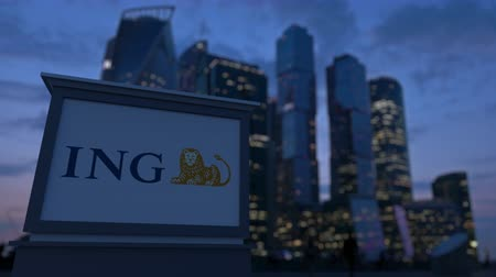 ing : Street signage board with ING Group logo in the evening.  Blurred business district skyscrapers background. Editorial 3D rendering Stock mozgókép