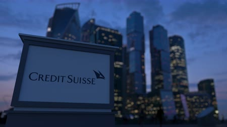 credit suisse : Street signage board with Credit Suisse Group logo in the evening.  Blurred business district skyscrapers background. Editorial 3D rendering Stock Footage