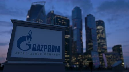 gazprom : Street signage board with Gazprom logo in the evening.  Blurred business district skyscrapers background. Editorial 3D rendering