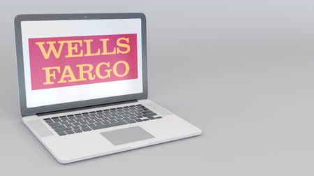 címer : Rotating opening and closing laptop with Wells Fargo logo. Computer technology conceptual editorial clip