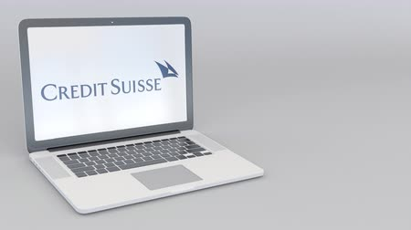 credit suisse : Rotating opening and closing laptop with Credit Suisse Group logo. Computer technology conceptual editorial