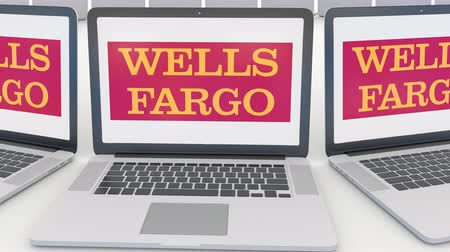 scandal : Laptops with Wells Fargo logo on the screen. Computer technology conceptual editorial clip, seamless loop