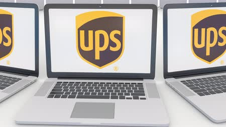 marca : Laptops with United Parcel Service UPS logo on the screen. Computer technology conceptual editorial clip, seamless loop