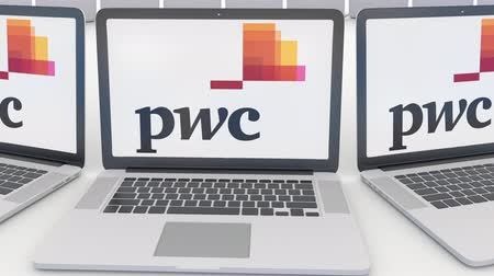 pwc : Laptops with PricewaterhouseCoopers PwC logo on the screen. Computer technology conceptual editorial clip, seamless loop