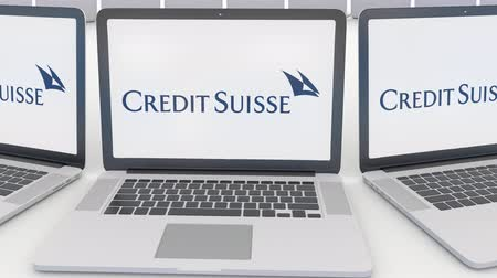 credit suisse : Laptops with Credit Suisse Group logo on the screen. Computer technology conceptual editorial clip, seamless loop Stock Footage