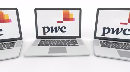 pwc : Notebooks with PricewaterhouseCoopers PwC logo on the screen. Computer technology conceptual editorial  clip, seamless loop Stock Footage