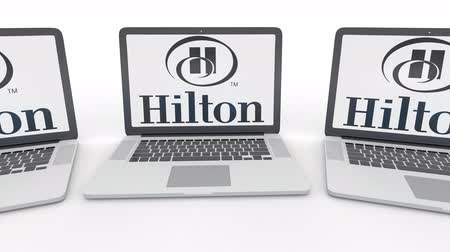 hilton : Notebooks with Hilton Hotels Resorts logo on the screen. Computer technology conceptual editorial  clip, seamless loop Stock Footage
