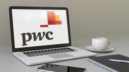 pwc : Opening laptop with PricewaterhouseCoopers PwC logo on the screen. Modern workplace conceptual editorial Stock Footage