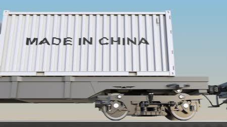 készült : Moving cargo train and containers with MADE IN CHINA caption. Railway transportation. Seamless loop 4K clip