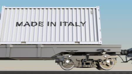 коммерция : Moving cargo train and containers with MADE IN ITALY caption. Railway transportation. Seamless loop 4K clip Стоковые видеозаписи