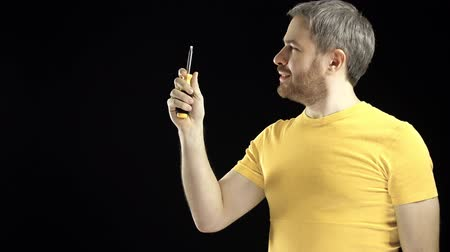 kutilství : Cheerful man in yellow tshirt holds screwdriver. DIY, repair, amateur construction or home improvement concepts. Black background. 4K video