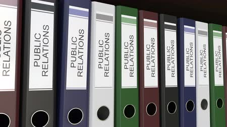 hírnév : Line of multicolor office binders with Public relations tags. 4K seamless loop clip