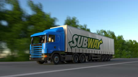 franczyza : Freight semi truck with Subway logo driving along forest road, seamless loop. Wideo