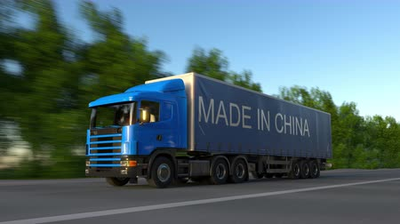 készült : Speeding freight semi truck with MADE IN CHINA caption on the trailer. Road cargo transportation. Seamless loop 4K clip